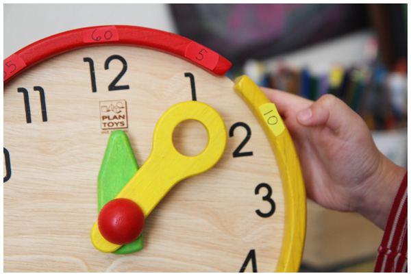 Teaching kids to tell time with the wooden Plan Toys Activity Clock