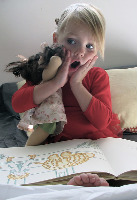 girl reading to her doll