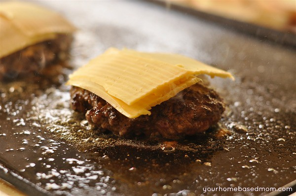hamburger on a grill topped with cheese