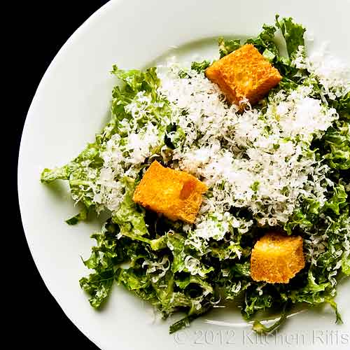 Chopped Kale Salad with Crouton Garnish, Overhead View on Black