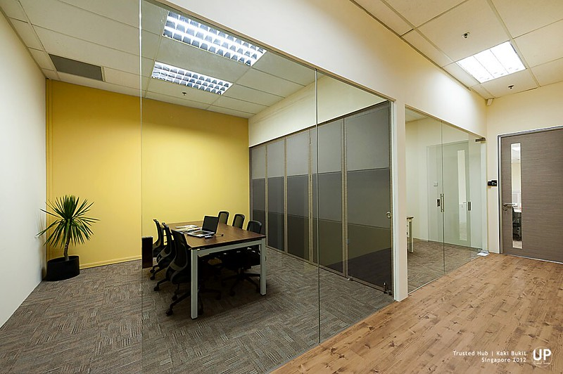 Discussion room with yellow highligh wall and corridor to working area
