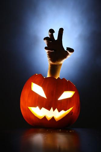Hand raising from pupmkin lantern