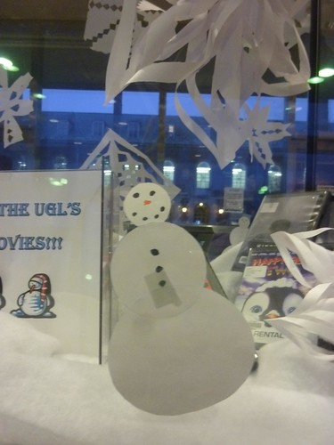 A paper snowman greets you from a glass display case.
