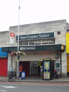 "A small railway station entrance built of Portland stone. The words ""West Croydon Station"" are on a sign above the entrance in white text on a dark green background. A protruding sign shows the National Rail symbol and the letters ""on""."