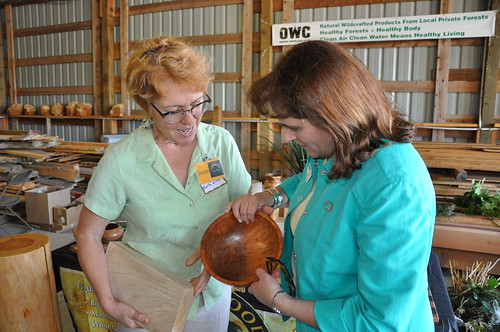 "Susan Curington of North Woods Figured Woods (left) shows State Director Vicki Walker (right) how the family business ""upcycles"" burls, stumps and small, odd-shaped, or difficult-to-use wood pieces to be sold at premium prices to carvers and other hobbyists. USDA photo."
