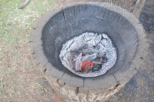 A kiti, being made in this picture, is a wooden mortise that Native Americans use to pound corn into hominy.