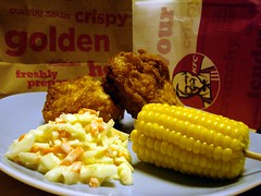 A pale blue plate containing two pieces of golden battered fried chicken, a mound of coleslaw, and half a corn cob on a wooden stick.  Paper bags with KFC branding are visible in the background.