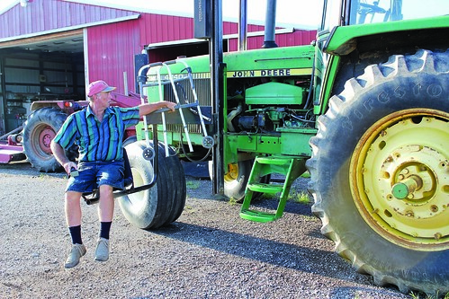 Mark Hosier, paralyzed from the waist down, uses a mechanical lift to board his tractor. Hosier works with the NIFA-funded AgrAbility Program to overcome disabilities and continue working as an agricultural producer.  Photo courtesy of National Swine Registry/Seedstock EDGE.