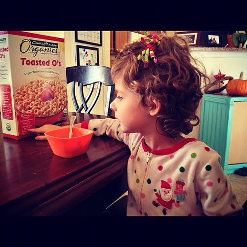 Ruby reading the cereal box at breakfast. #shelovestoread