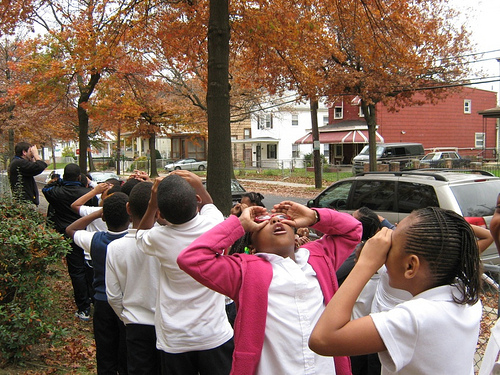 "Local children from the Paul Public Charter School in Washington, D.C., take to the streets pretending to use binoculars in search of their urban forest. Washington D.C. was one of the top cities highlighted in the NY Times ""Top 10 Urban Forests""."