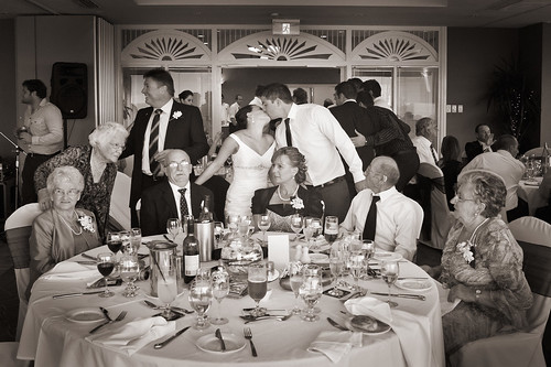 Bride and groom kissing amongst guests.