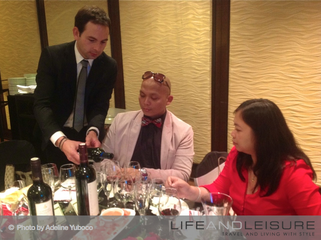 ASEAN Merchants' David Coll-Piferrer pours a glass of Spanish wines for the guests to try