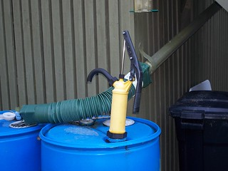 Rain barrels with diverter and hand pump