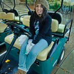 12-072 -- Shuttle driver Anyssa Balcazar '16 huddles under cover on her cart during the rain while waiting for a passenger.