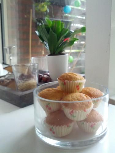 Kleine lichte cupcakes in witte papiertjes met kersjes er op zitten in een glazen schaal met dikke rechte wanden. De schaal staat op een vensterbank, naast wat plantjes en kaarsen, en een wit strak beeldje van een dikke kat. Door het raam heen zie je enkele (klim)planten en lampions hangen.