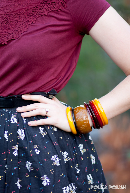 A stack of bakelite bangles in red, yellow, and brown hues echoes the autumn colors of this vintage-inspired outfit