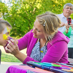 12-043-5 -- Judy Nord, face painter with the Zoo Crew, works on 6-year-old Cole while his grandparents -- IWU President Richard F. Wilson and Dr. Pat Wilson -- shoot some video.