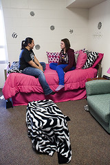 Picture of bed with 2 females students sitting