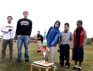 Middle schoolers discussing fine points of rocket design while Vandy engineering students Brock Smethills, right, and Jason Lee look on.