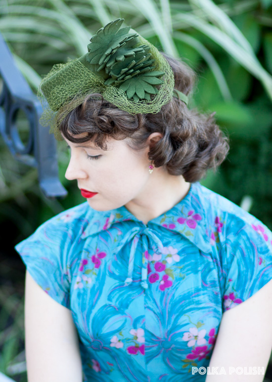 Cut felt flowers grace the side of a moss green 1940s tilt hat