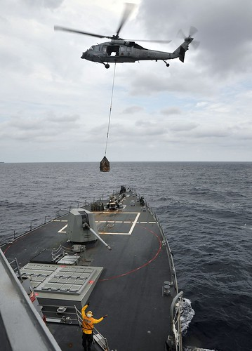Boatswain's Mate 3rd Class Gerald Battle signals to an MH-60S Sea Hawk helicopter conducting a vertical replenishment