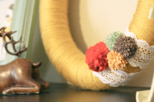 Yarn wreath with lace and pom-poms