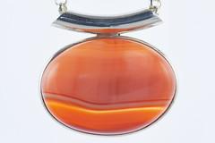glass bottle(0.0), glass(0.0), amber(1.0), orange(1.0), amber(1.0), jewellery(1.0), gemstone(1.0), pendant(1.0),