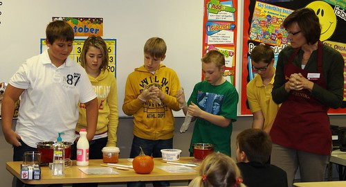 Bonnie Chirstenson from University of Minnesota Extension (far right) shows students in Mrs. Jones' sixth-grade class in Tracy Elementary how to make pumpkin pudding using a locally grown pumpkin.