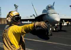 Aviation Boatswain's Mate (Handling) Cephas Banini directs fixed-winged aircraft aboard the aircraft carrier USS Nimitz (CVN 68) during the ship's Joint Task Force Exercise (JTFEX), Nov. 11. (U.S. Navy photo by Mass Communication Specialist 2nd Class Benjamin Crossley)