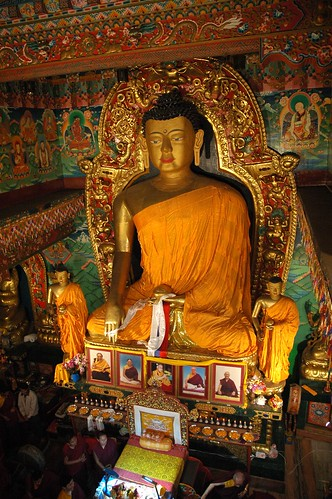 Statue of Lord Buddha with chief students, His Holiness Jigdal Dagchen Sakya climbs down from his throne, photos of renown lamas, bowls of nectar offerings with marigolds, lights, aura, Sakya lineage lords, monks, Tharlam Monastery, Boudha, Nepal by Wonderlane