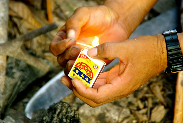 lighting fire with match in the amazon