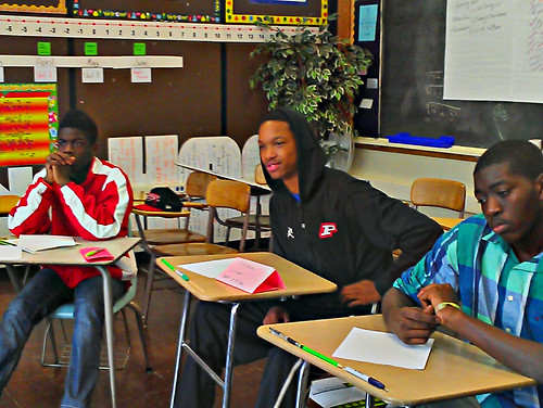 Young men listen to a student share his lyrics during a self-expression session.