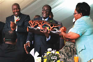 President Mugabe is helped by Vice-President Mujuru to receive a gift from Mwana Africa's Chief Executive Mr Kalaa Mpinga while Youth Development, Indigenisation, and Economic Empowerment Minister Saviour Kasukuwere looks on at the Bindura Community. by Pan-African News Wire File Photos