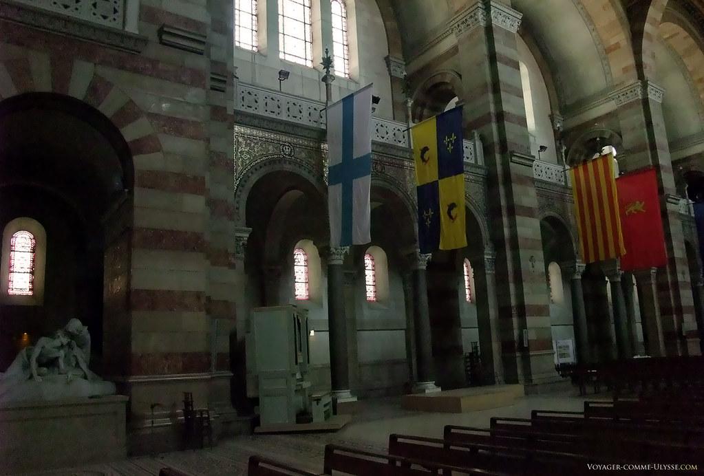 Les drapeaux présents dans la nef représentent les différentes régions de France. On distingue l'œuvre du sculpteur de Marseille, Auguste Carli, Véronique essuyant la face de Jésus tombé à terre.