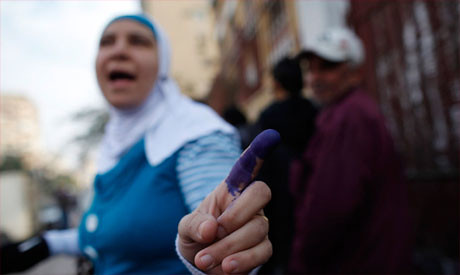 Egyptian voter shows blue finger during poll on draft constitution. The opposition National Salvation Front says the vote was rigged and that 66 percent voted no. by Pan-African News Wire File Photos