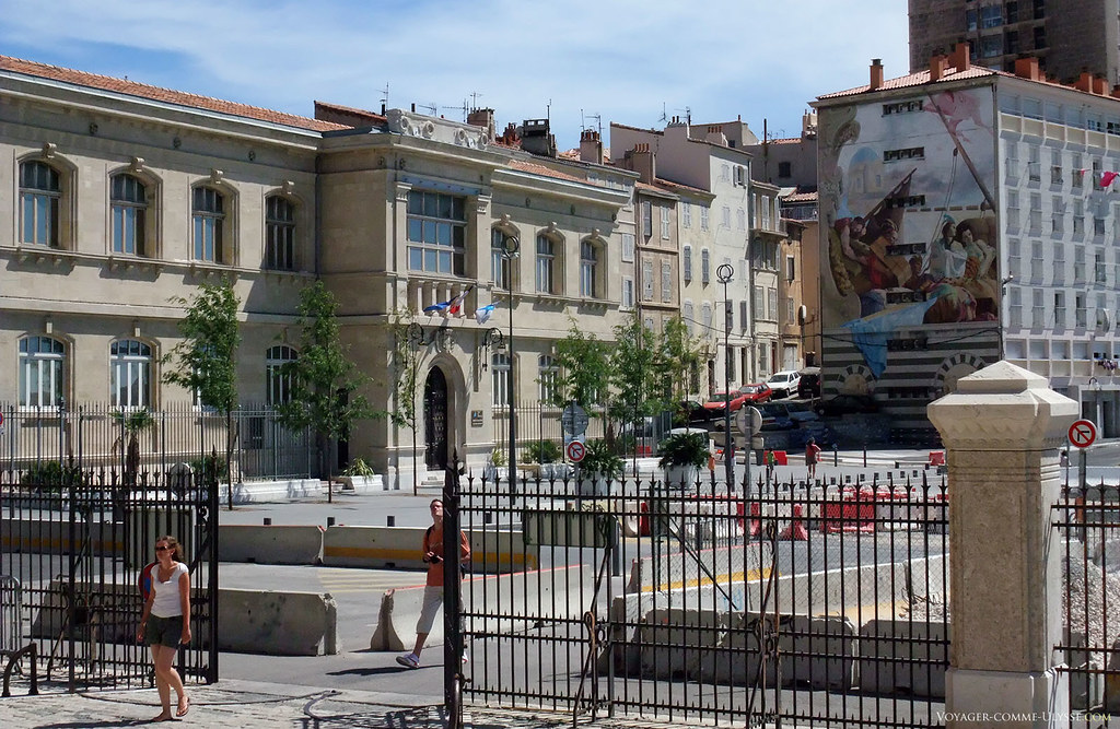 De l'autre coté de la Place de la Major se trouve, ici sur la gauche, la mairie des 2ème et 3ème arrondissements de Marseille. A droite, la grande peinture murale occupe tout le coté de cet immeuble.