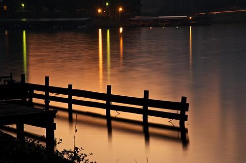 longexposure orange lake water sunrise lights dock shadows
