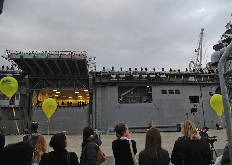 Family and friends await Sailors to depart the amphibious assault ship USS Bonhomme Richard (LHD 6)