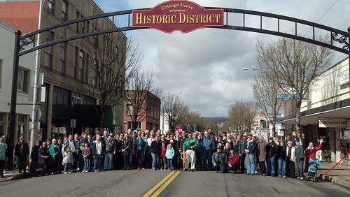 Cottage Grove residents stand under an arch welcoming visitors to the newly restored downtown area.