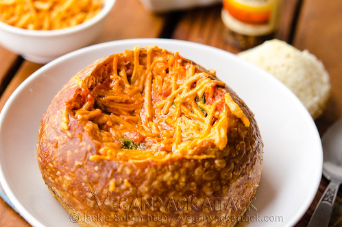 A comforting meal of tomato spinach soup in a toasted sourdough bowl, topped with melted cheddar shreds; AKA the Tomato Spinach Grilled Cheese Bread Bowl!