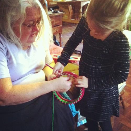 Grandma teaching Bug how to Knifty knit.