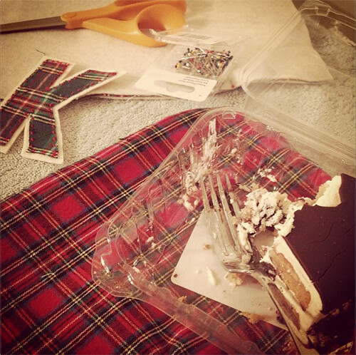 Plaid fabric with scissors and pins in the background, along with a sewn letter K. In the foreground is a container with a half-eaten piece of cake.