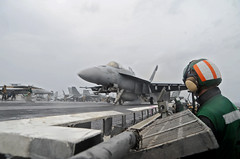 Aviation Boatswain's Mate (Equipment) 2nd Class Ben Shaw watches an F/A-18E Super Hornet from the Dambusters of Strike Fighter Squadron (VFA) 195 launch from the flight deck aboard the U.S. Navy's forward-deployed aircraft carrier USS George Washington (CVN 73) during the Carrier Air Wing 5 flyoff, Nov. 17. (U.S. Navy photo by Mass Communication Seaman Brian H. Abel)