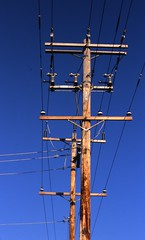 electronic device(0.0), television antenna(0.0), vehicle(0.0), mast(0.0), tower(0.0), antenna(0.0), electrical supply(1.0), overhead power line(1.0), line(1.0), transmission tower(1.0), electricity(1.0), blue(1.0), public utility(1.0),
