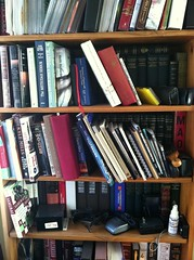 Papi's bookshelf: political fiction, histories, Latin jazz CDs, and old camera parts. Classic.