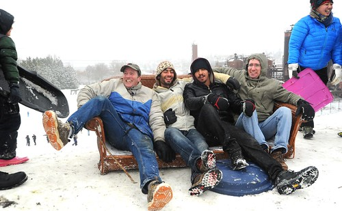 Snow day laughter, 4 guys in their sofa sled, couch surfing, winter wear, garbage can lid, on top of the hill, snow day, Gasworks Park, Wallingford, Seattle, Washington, USA by Wonderlane