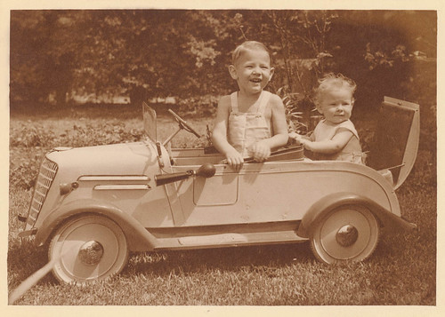 Boy in pedal car with baby in 'rumble seat', Sydney, ca. 1935 / photographer Sam Hood