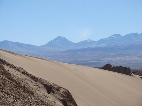 Le désert d'Atacama: vue sur des volcans enneigés et dont un fume depuis la Vallée de la Mort