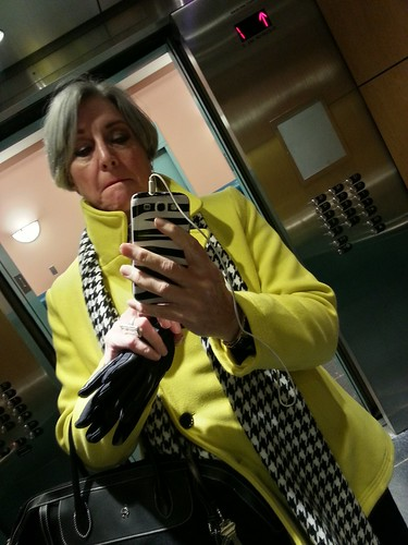 DarkEmeralds in an elevator, wearing a sulfur yellow coat with black and white accessories