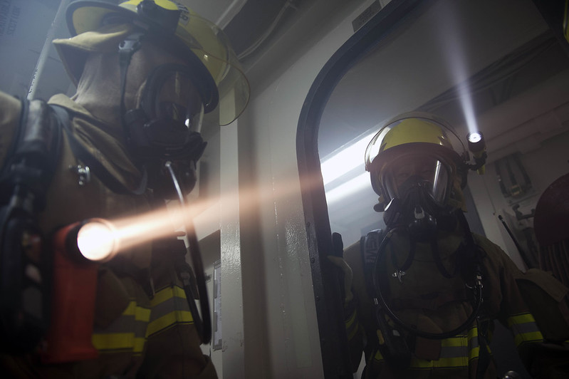 Firefighters from Fleet Activities Yokosuka's fire and emergency services prepare to enter an smoke-filled space
